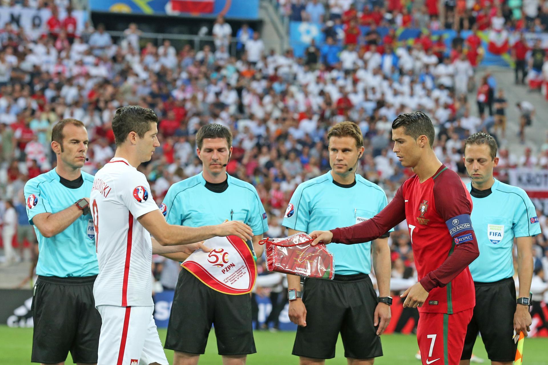 Robert Lewandowski i Cristiano Ronaldo - kapitanowie obu drużyn i dwie wielkie gwiazdy światowego futbolu wymieniają proporczyki przed ćwierćfinałowym starciem w Marsylii.