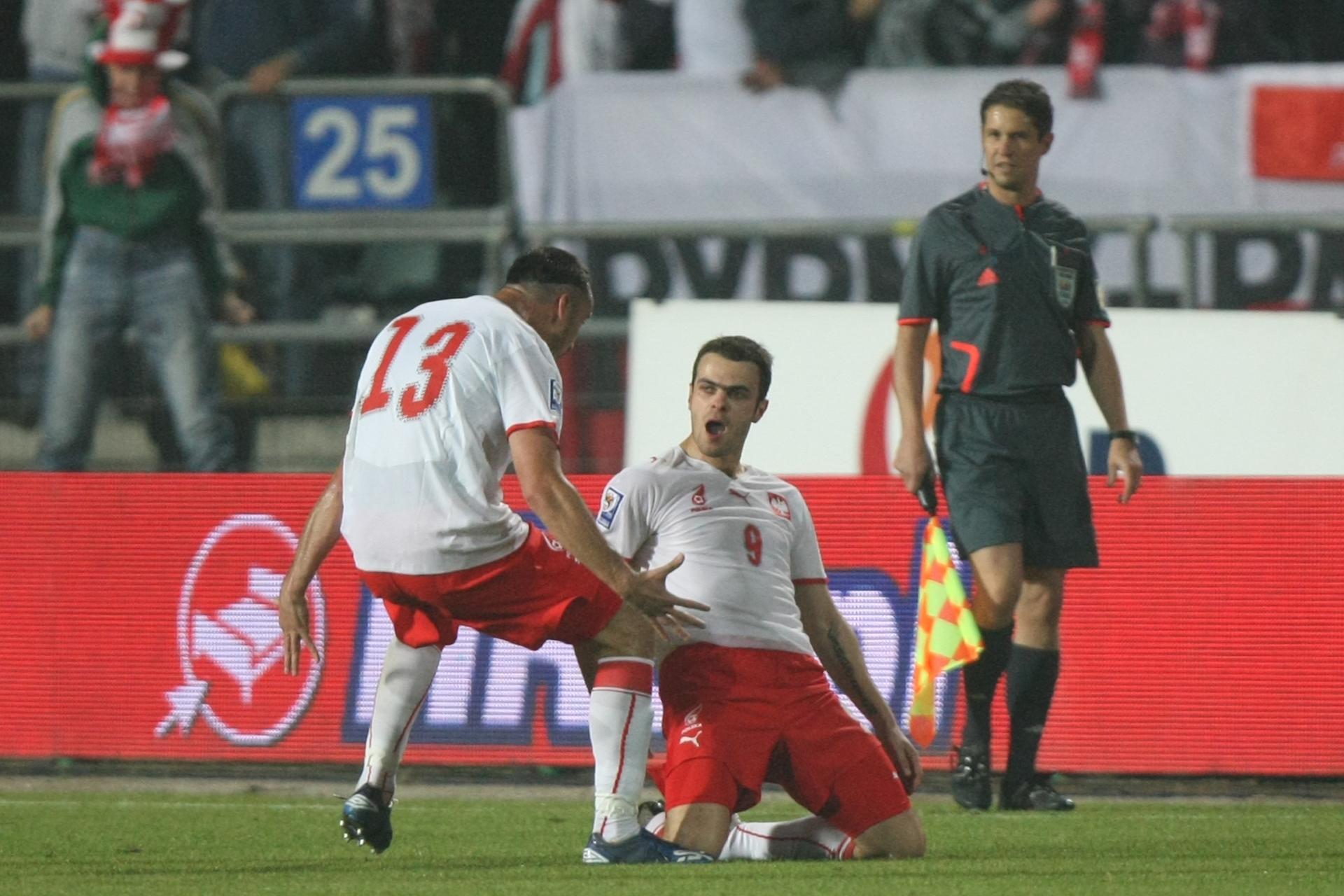 Paweł Brożek na kolanach po zdobyciu bramki. Z gratulacjami pędzi do niego Marcin Wasilewski.