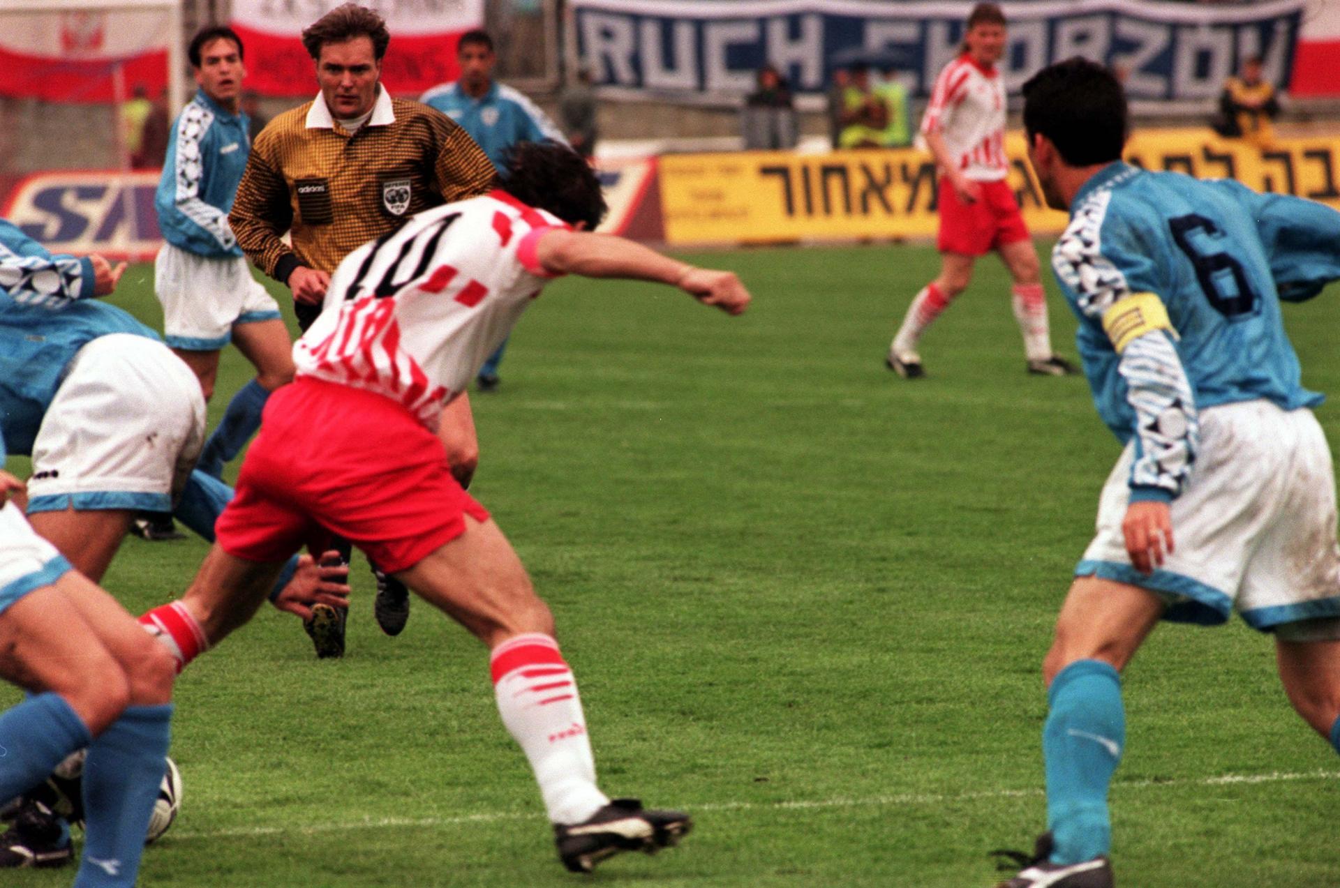 Sędzia Anders Frisk przygląda się walczącemu o piłkę Romanowi Koseckiemu.