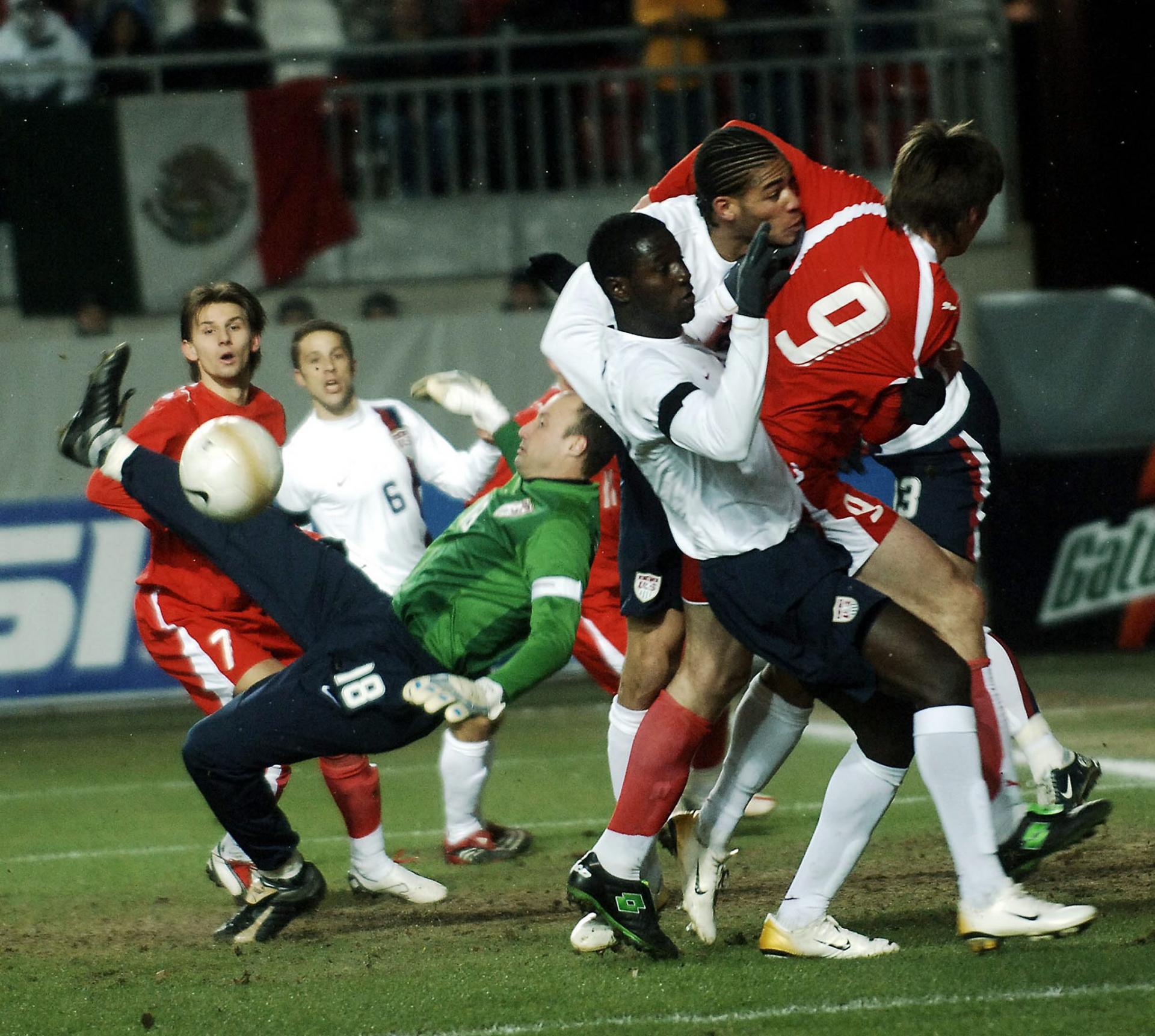 Grzegorz Rasiak powstrzymywany przez Amerykanów podczas meczu USA - Polska 1:0 (01.03.2006).