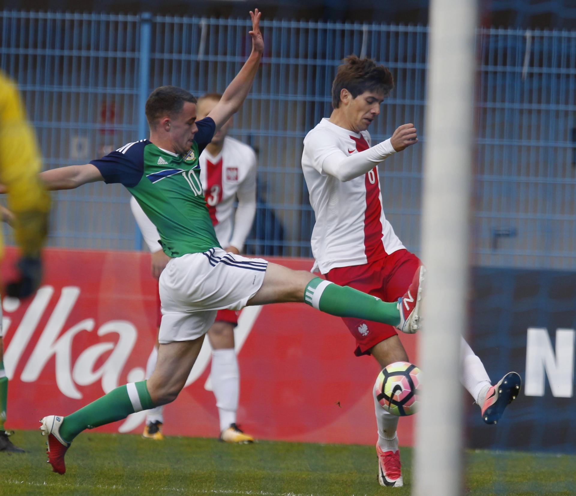 Jakub Moder powstrzymywany przez zawodnika Irlandii Północnej. Mecz eliminacji mistrzostw Europy drużyn do lat 19.