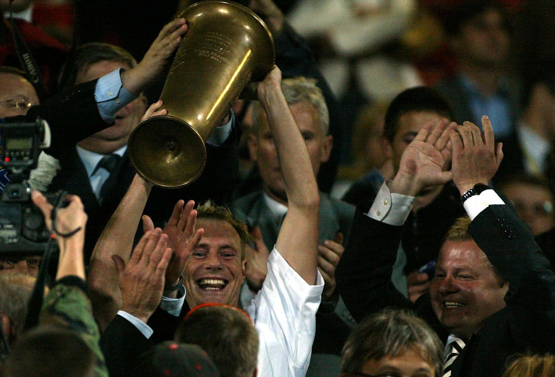 Piotr Reiss wznosi trofeum za zwycięstwo w finale Pucharu Polski w 2004 roku.