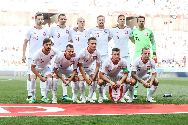 Reprezentacja Polski (w białych strojach) pozuje do zdjęcia przed meczem z Japonią. Bramkarz Łukasz Fabiański w jaskrawo-zielonym stroju.