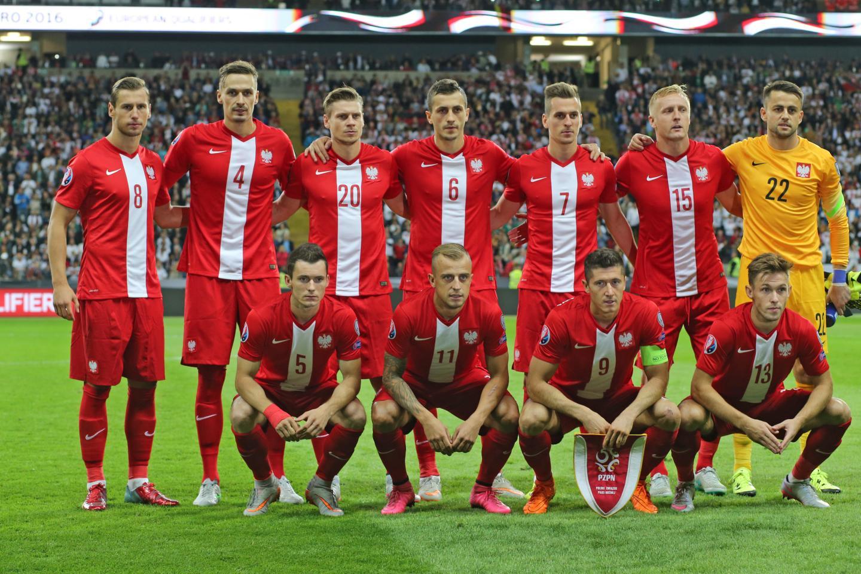 Reprezentacja Polski w czerwonych strojach (koszulki z białym pasem pośrodku oraz orzełkiem na piersi) przed meczem z Niemcami. Łukasz Fabiański (pierwszy z prawej u góry) ubrany w żółty strój.