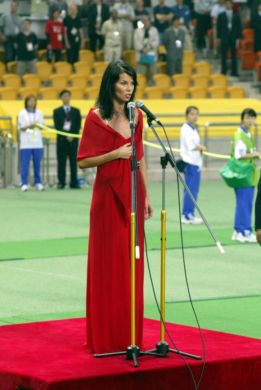 Edyta Górniak, ubrana w czerwoną sukienkę, śpiewa hymn Polski przed meczem MŚ 2002 z Koreą Południową.