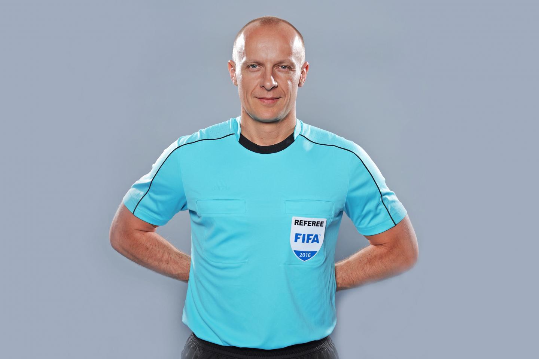 Sędzia Szymon Marciniak ubrany w jasnoniebieską koszulkę i czarne spodenki. Sesja przed Euro 2016.