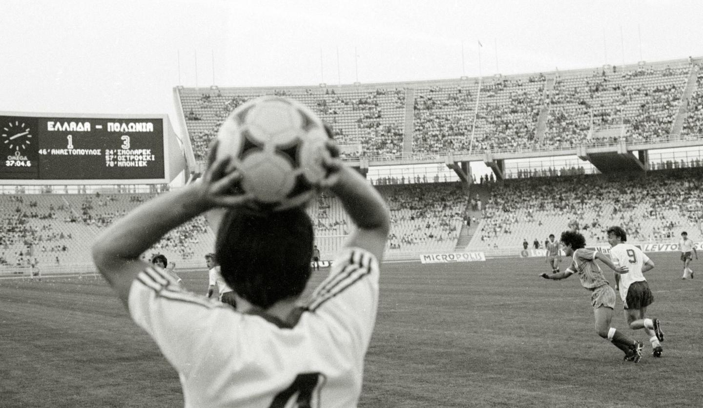 Widok stadionu w Atenach zza pleców piłkarza.