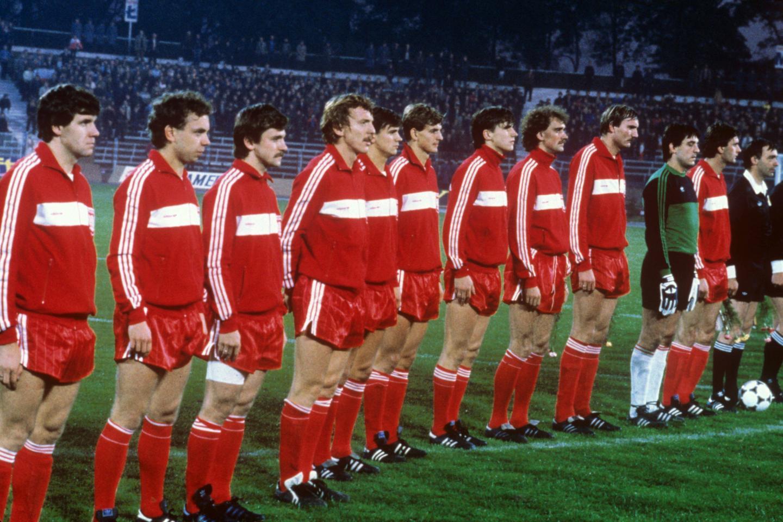 Reprezentacja Polski w czerwonych bluzach dresowych z białym poziomym pasem, czerwonych spodenkach i czerwonych getrach. Zdjęcie przed meczem z Grecją na stadionie Górnika Zabrze w 1984 roku.