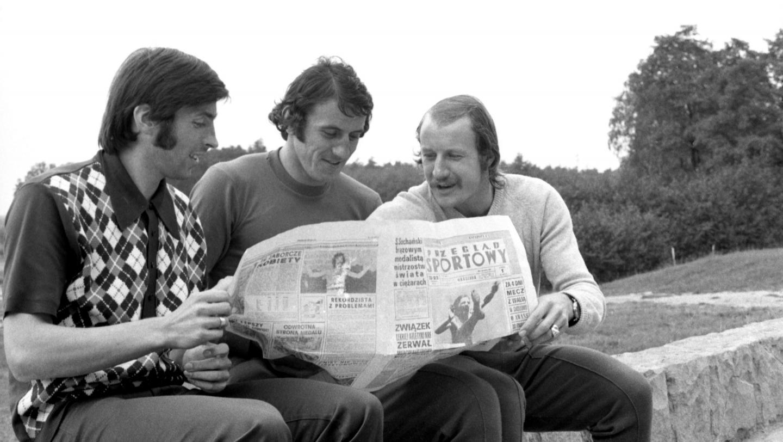 Kazimierz Deyna, Adam Musiał i Robert Gadocha przeglądający wspólnie gazetę.