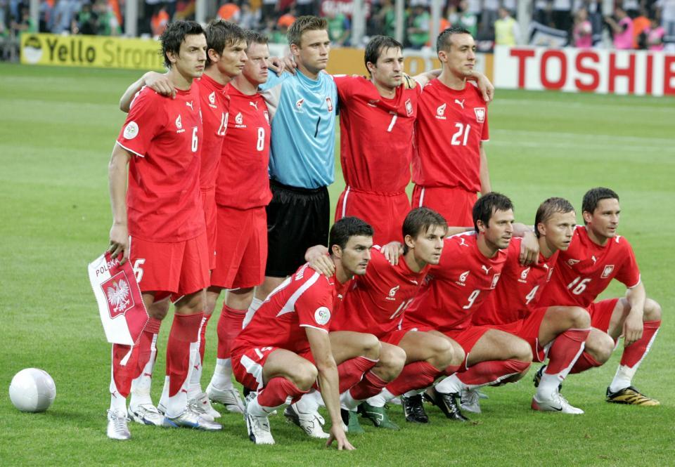 Reprezentacja Polski, w czerwonych strojach, pozuje do zdjęcia przed meczem z Niemcami. Artur Boruc w błękitnej bramkarskiej bluzie i czarnych spodenkach.