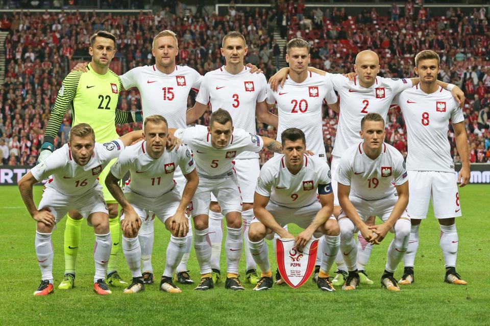 Reprezentacja Polski przed meczem z Danią w Kopenhadzie. Polacy w białych strojach. Łukasz Fabiański w żółtawym stroju bramkarskim z czarnymi poziomymi paskami na rękawach.