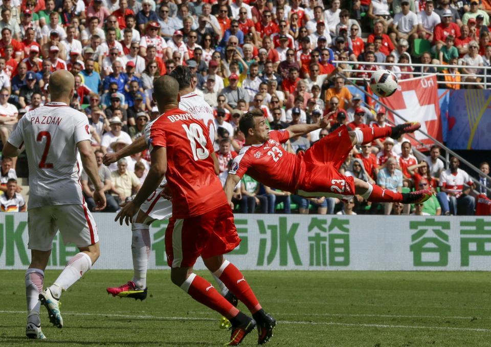 Xherdan Shaqiri uchwycony w momencie oddawania strzału przewrotką, po którym padła bramka dla Szwajcarii na 1:1. Szwajcarzy na czerwono, Polacy na biało.