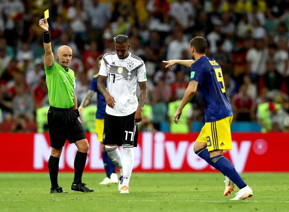 Szymon Marciniak pokazuje żółtą kartkę piłkarzowi Szwecji.