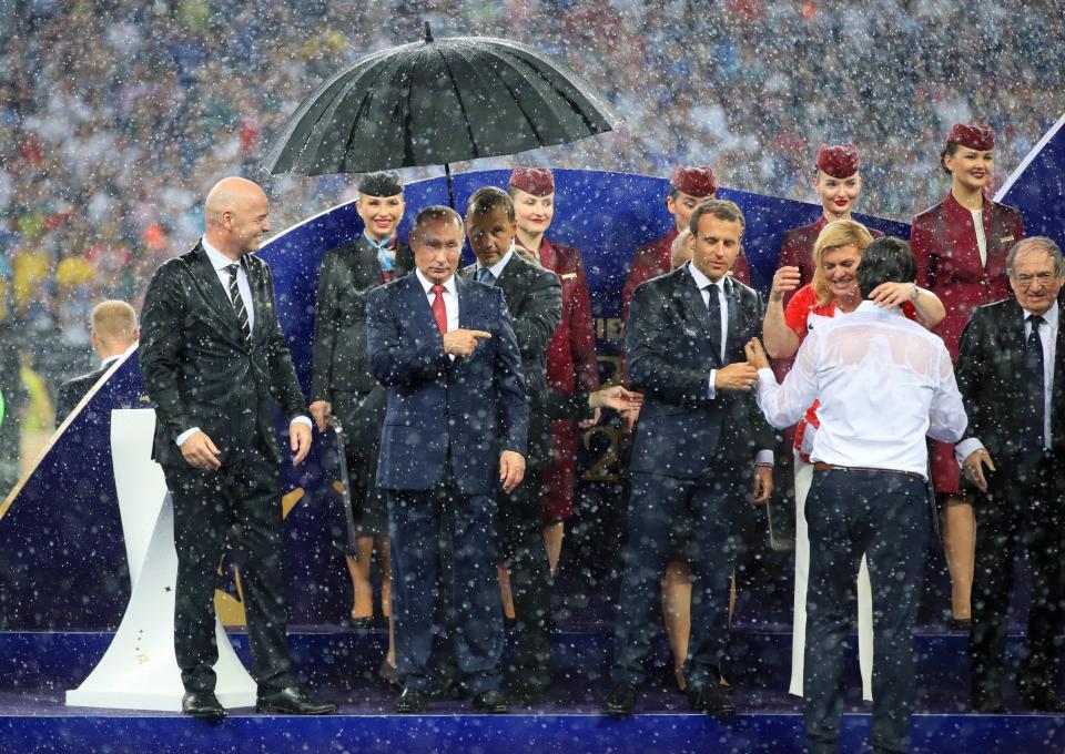 Władimir Putin osłonięty parasolem.