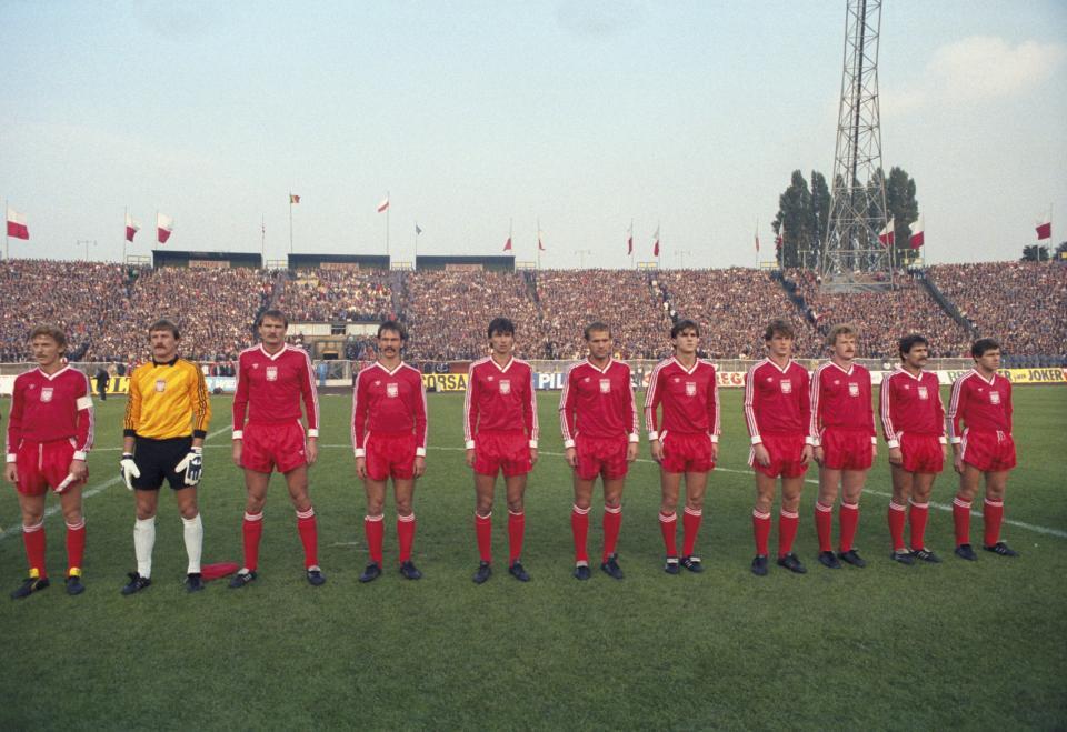 Reprezentacja Polski w czerwonych strojach przed meczem z Belgią na Stadionie Śląskim w Chorzowie. Bramkarz Józef Młynarczyk w żółtej bluzie, czarnych spodenkach i białych getrach.