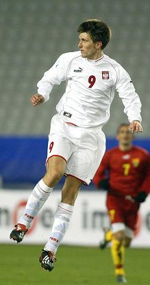 Grzegorz Rasiak w białym stroju reprezentacji Polski.