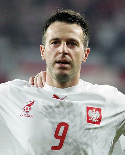 Maciej Żurawski w białej koszulce z husarzem.