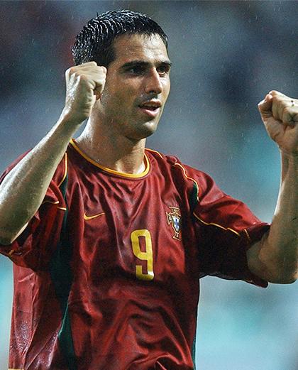 Pedro Pauleta (w bordowej koszulce) z rękoma uniesionymi w geście triumfu.