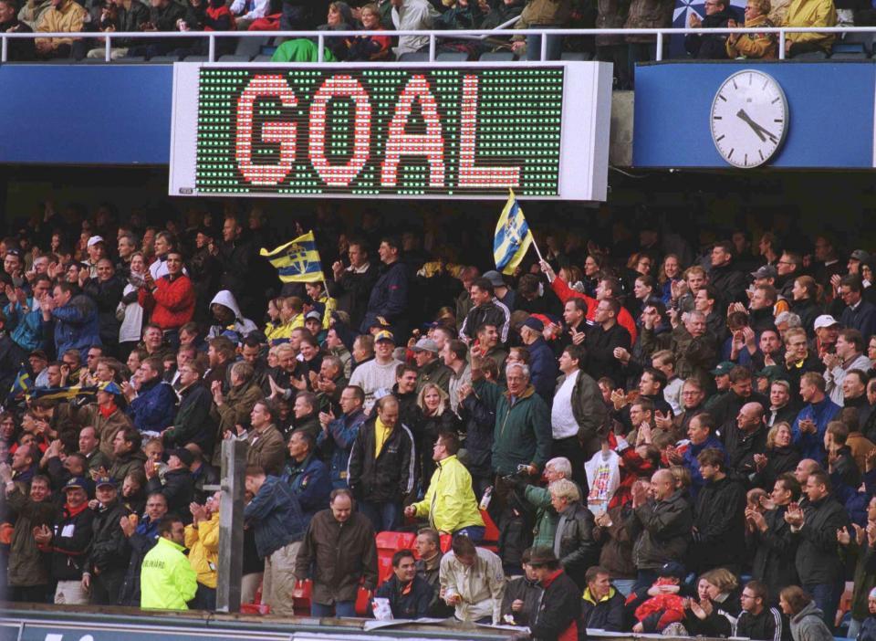 Kibice szwedzcy na sektorze pod tablicą świetlną, na której widnieje napis GOAL.