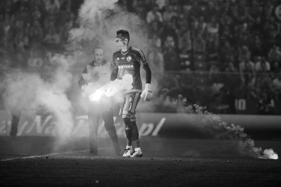 Arkadiusz Malarz podnoszący z murawy racę rzuconą przez kiboli Lecha Poznań podczas finału Pucharu Polski 2016.