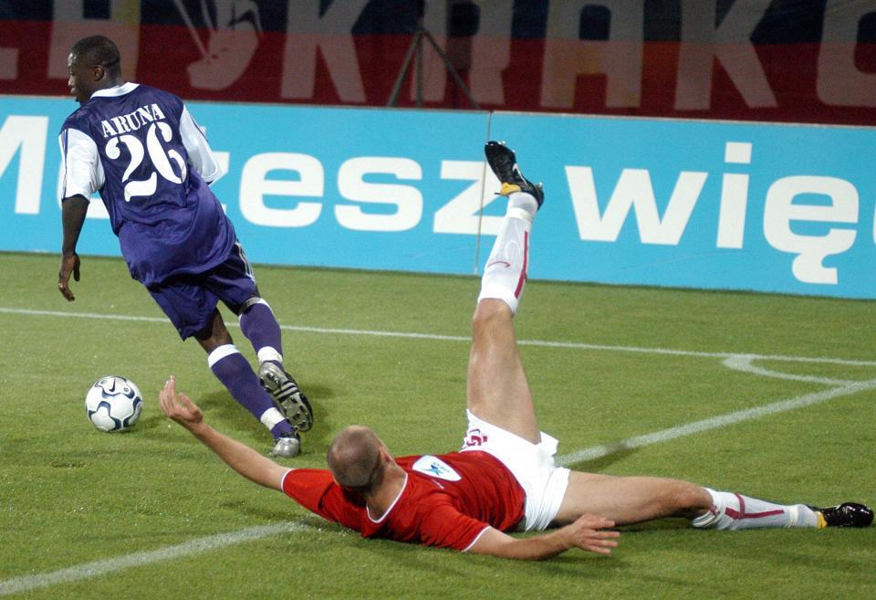 Aruna Dindané z Anderlechtu uciekający leżącemu na murawie zawodnikowi krakowskiej Wisły.