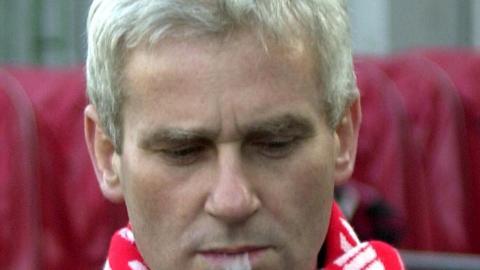 Były prezes PZPN Michał Listkiewicz palący cygaro.