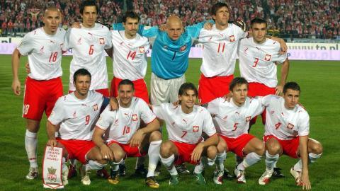 Reprezentacja Polski przed wygranym 2:1 meczem z Portugalią w Chorzowie. Polacy w białych koszulkach z husarzem oraz w czerwonych spodenkach.