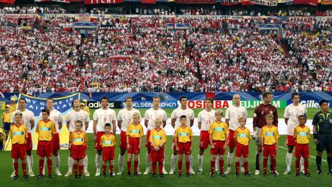 Reprezentacja Polski na środku boiska. Polacy w białych koszulkach, czerwonych spodenkach. Bramkarz Artur Boruc w bordowej bluzie. Przed piłkarzami stoją dzieci ubrane w żółte koszulki i czerwone spodenki.