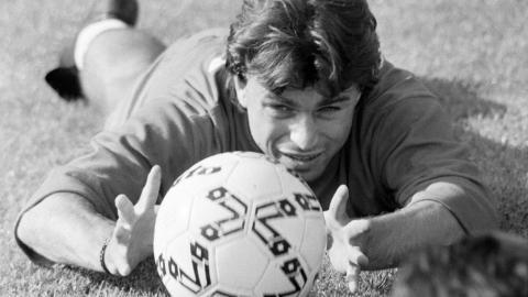 Roman Kosecki leżący na murawie i trzymający przed sobą piłkę.