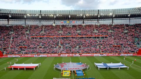 Reprezentacje Polski i Finlandii na boisku, w tle flagi obu państw. Towarzyskie spotkanie z 2016 roku.